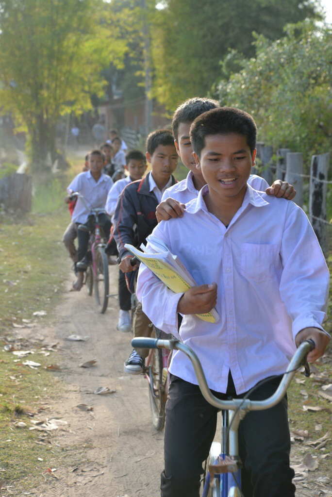 Kids coming home from school, often doubling or tripling up on a bike